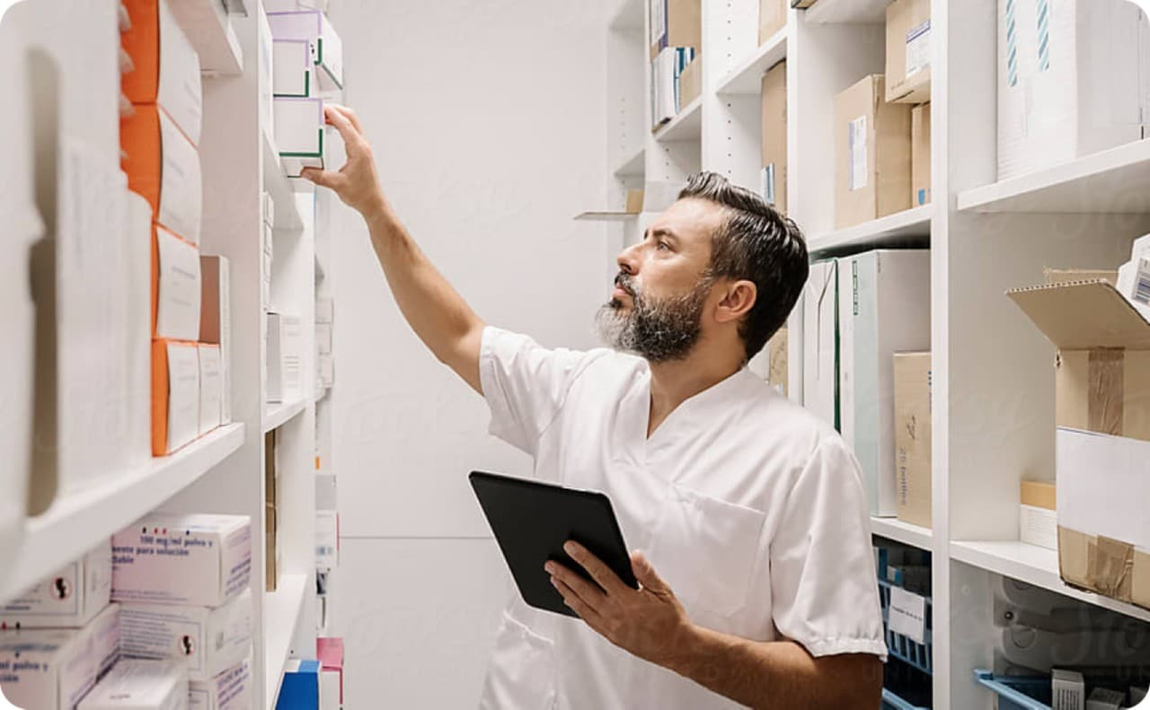 Man in white coat reaching for boxes in stock room.