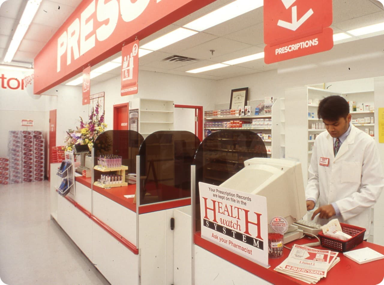 Inside of a Shoppers Drug Mart pharmacy with person working in white coat.
