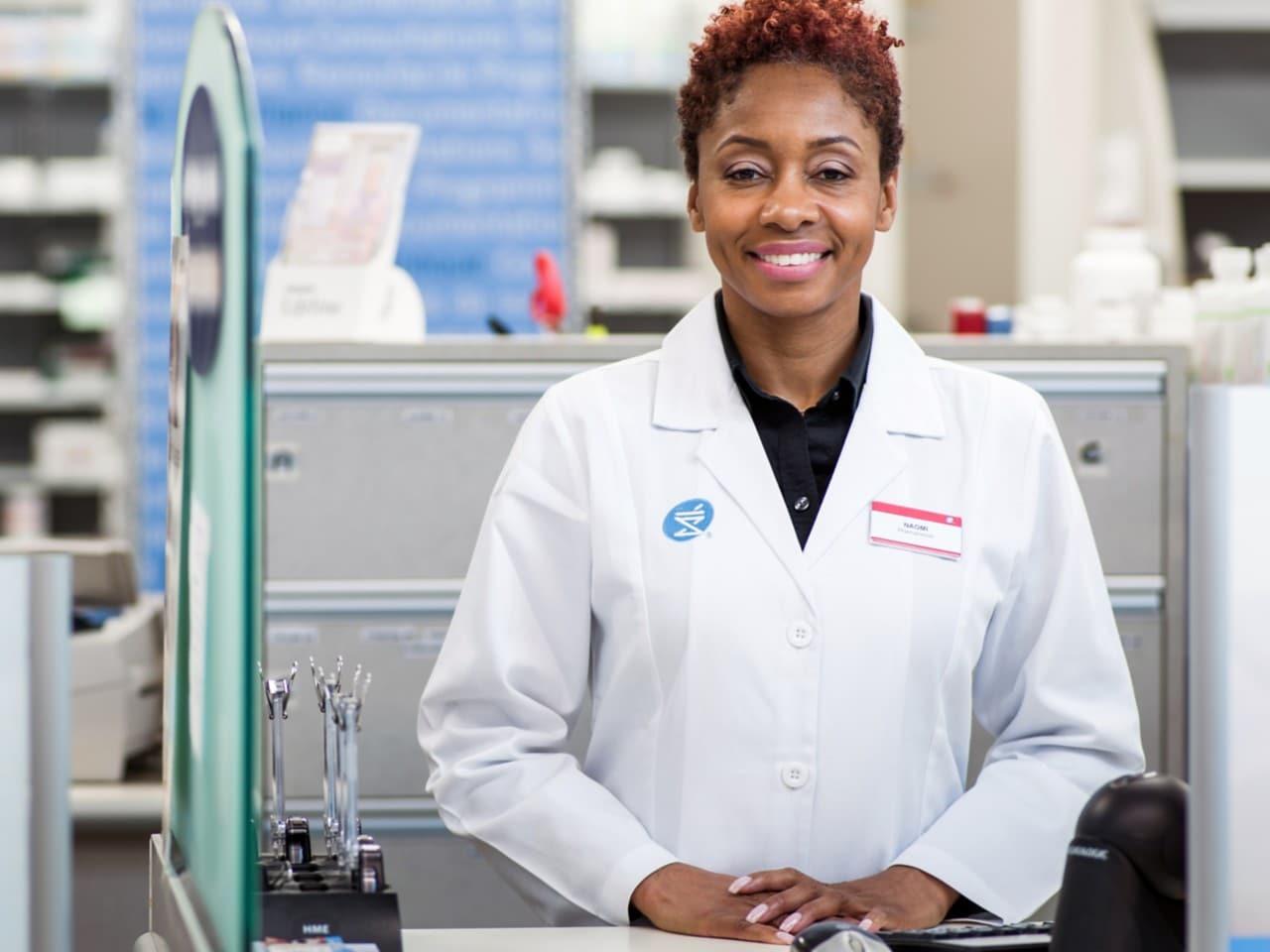 Une dame souriante vêtue d'un sarrau de pharmacie blanc
