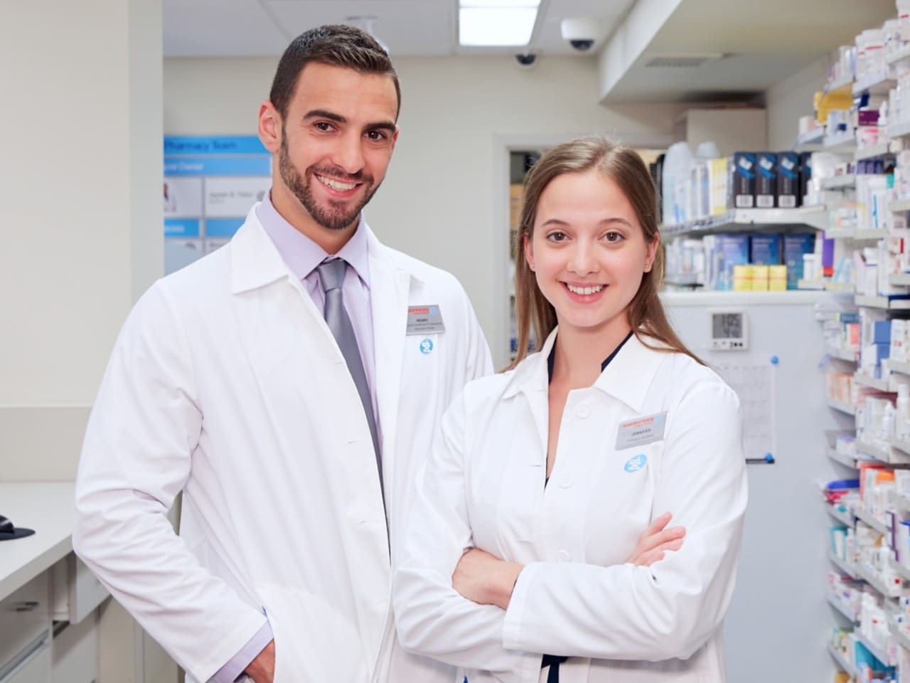 2 people in pharmacy jackets smiling