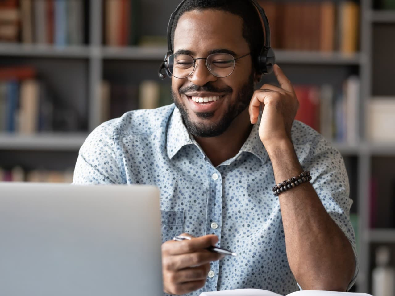 Man with glasses smiling at a desk with headset on