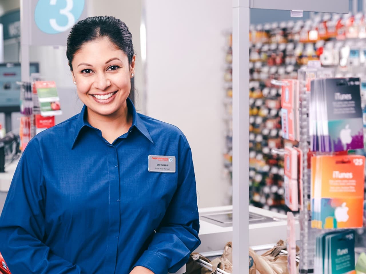 Woman smiling in a Shoppers Drug Mart wearing blue colllared shirt