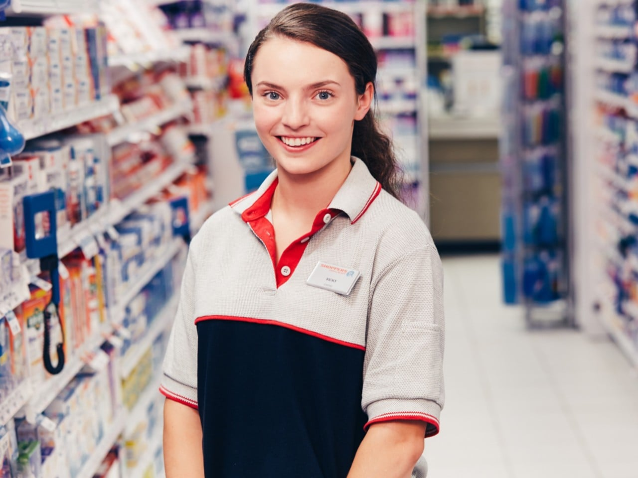 Smiling Shoppers Drug Mart empoyee wearing grey polo shirt.